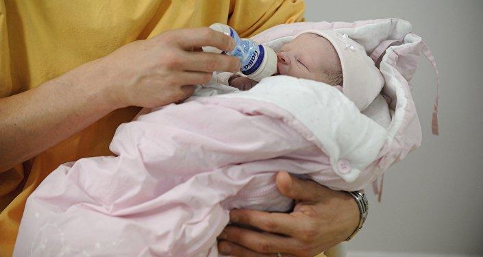 Женщина кормит новорожденного ребенка. Архивное фото