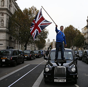Мужчина машет флагом Великобритании стоя на автомобиле