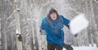 Архивное фото парня, играющего в снежки