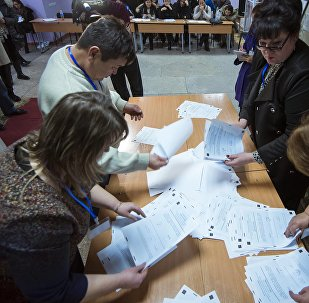 Сотрудники ТИК во время подсчета голосов на выборах в местные кенеши и референдум в избирательном участке №1209 в Бишкеке