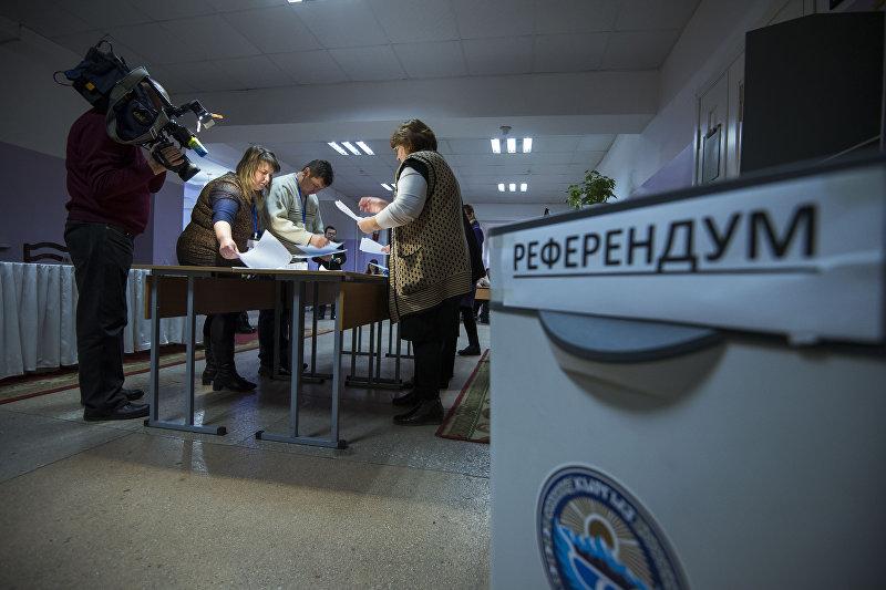 Сотрудник ТИК во время подсчета голосов на выборах в местные кенеши и референдум в избирательном участке №1209 в Бишкеке