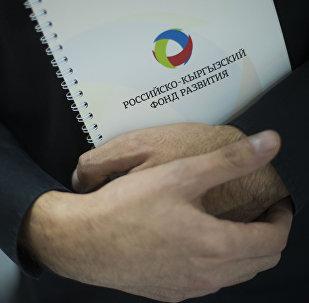 Мужчина держит папку с логотипом Российского-Кыргызского фонда развития (РКФР)