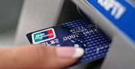 Женщина вставляет карточку в банкомат. Архивное фото
