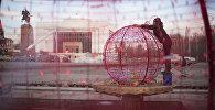 Сотрудники муниципальной службы устанавливают новогодние гирлянды на площади Ала-Тоо в Бишкеке