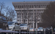 Отражение в луже воды автомобилей возле здания Жогорку Кенеша. Архивное фото