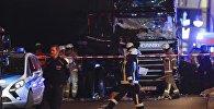 Спасатели и сотрудники правоохранительных органов на месте наезда грузовика на посетителей рождественской ярмарки в Берлине