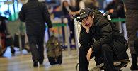 Пассажир сидит на багажной тележке в аэропорту. Архивное фото