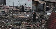 Сотрудник полиции разговаривает по мобильному телефону, стоя среди обломков домов, разрушенных в результате взрыва фейерверков за пределами мексиканской столицы во вторник, в Тультепек, Мексика. 20 декабря 2016 года