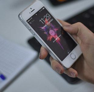 Колунда iPhone кармап турган кыз. Архив
