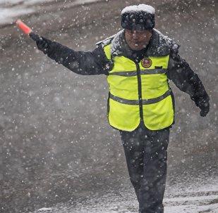 Сотрудник Патрульной милиции регулирует движение во время затора на дороге Бишкека. Архивное фото