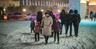 Женщина с детьми идет по улице во время снегопада. Архивное фото