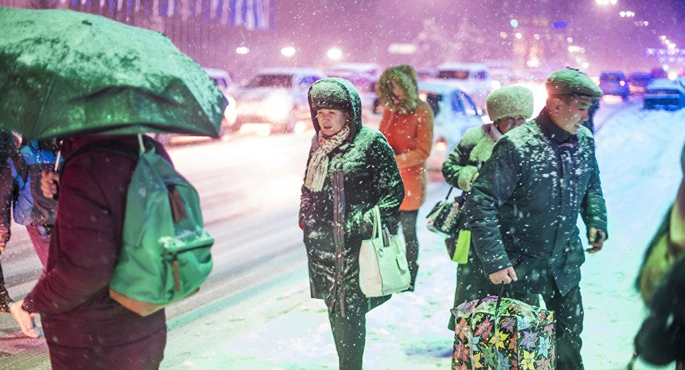 Архивное фото жителей Бишкека, которые ожидают транспорт во время снегопада