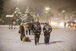 Жители Бишкека во время снегопада. Архивное фото