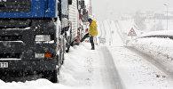 Водитель у застрявшего в снегу грузовика. Архивное фото
