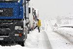 Водитель у застрявшего в снегу грузовика на заснеженной дороге. Архивное фото
