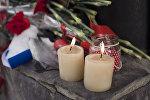 Цветы и свечи в посольстве России в Бишкеке в память о погибших во время крушения самолета Минобороны РФ