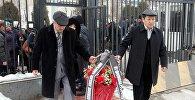 Люди несут цветы на панихиде и траурном митинге в память о жертвах крушения самолета Ту-154 под Сочи в Генконсульстве РФ в Оше