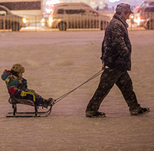 Архивное фото мужчины, катающий ребенка на санках в Бишкеке