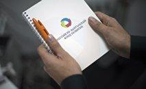 Мужчина держит блокнот с логотипом Российского-Кыргызского фонда развития (РКФР)