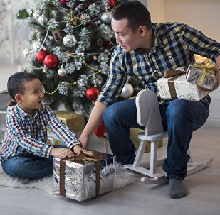 Отец дарит сыну подарки. Архивное фото