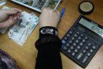 Женщина считает рубли на калькуляторе. Архивное фото