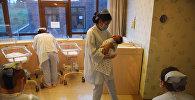 Сотрудница родильного дома с младенцем на руках. Архивное фото