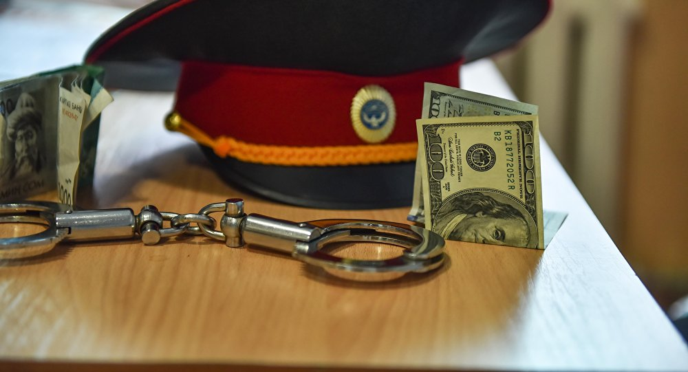 Милицейская фуражка, наручники и сто долларовая купюра на столе. Архивное фото