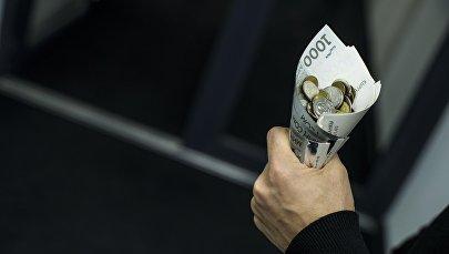 Мужчина держит кулек из денег с монетами. Архивное фото