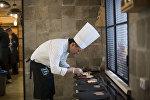 Профессиональный шеф-повар Виктор Цой во время работы на кухне. Архивное фото