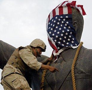 Солдат морской пехоты США закрывает голову статуи флагом США. Архивное фото