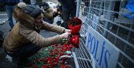 Девушка оставляет цветы снаружи ночного клуба, где в ночь на 1-ое января произошло нападение
