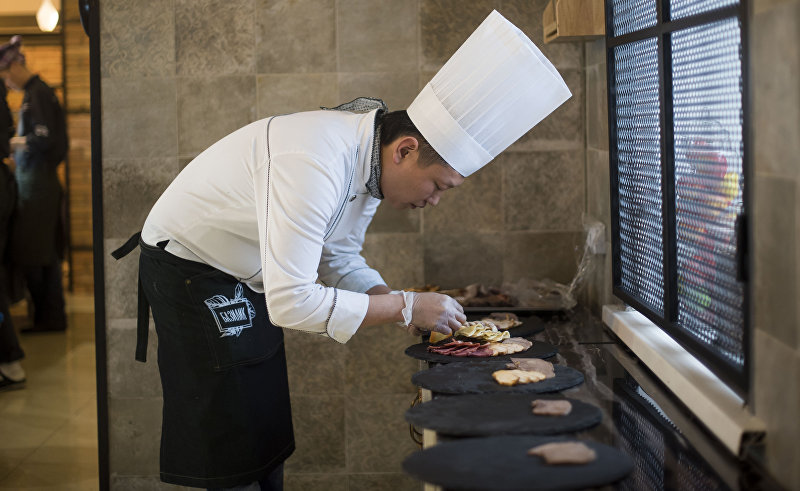 Профессиональный шеф-повар Виктор Цой во время работы на кухне