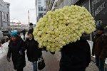 Мужчина несет цветы. Архивное фото