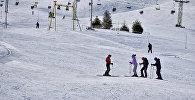 Тоо лыжа базаларынын биринде эс алып жаткан адамдар. Архив