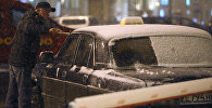 Водитель такси очищает лобовое стекло автомобиля от снега. Архивное фото