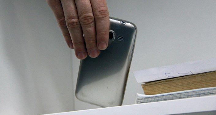 Мужчина берет телефон с полки. Архивное фото