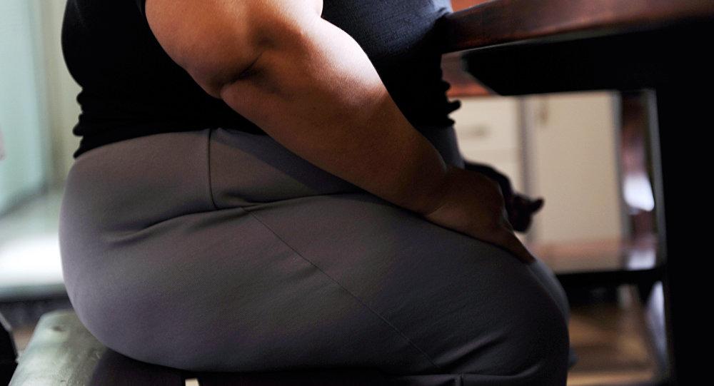 Женщина с лишним весом сидит за столом. Архивное фото