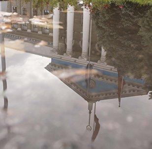 Отражение фасада здания мэрии города Бишкек в луже воды. Архивное фото