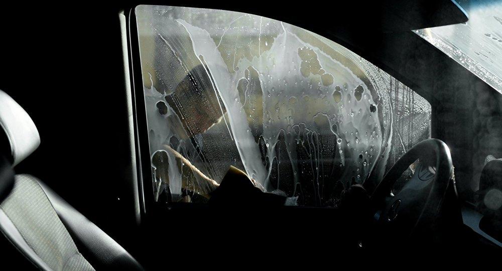 Рабочий моет машину на автомобильной мойке. Архивное фото