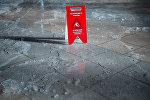 Предупреждающий знак Осторожно, гололед! на тротуаре. Архивное фото