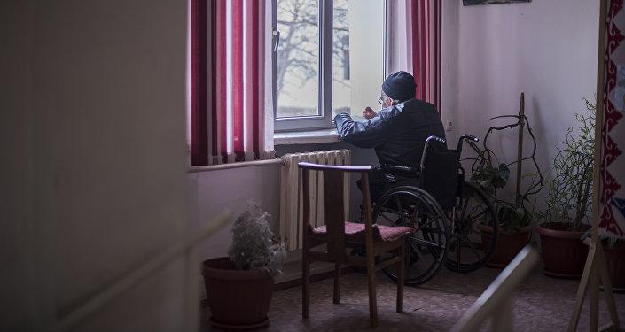 Пожилой мужчина в коляске у окна Бишкекского дома-интерната для престарелых