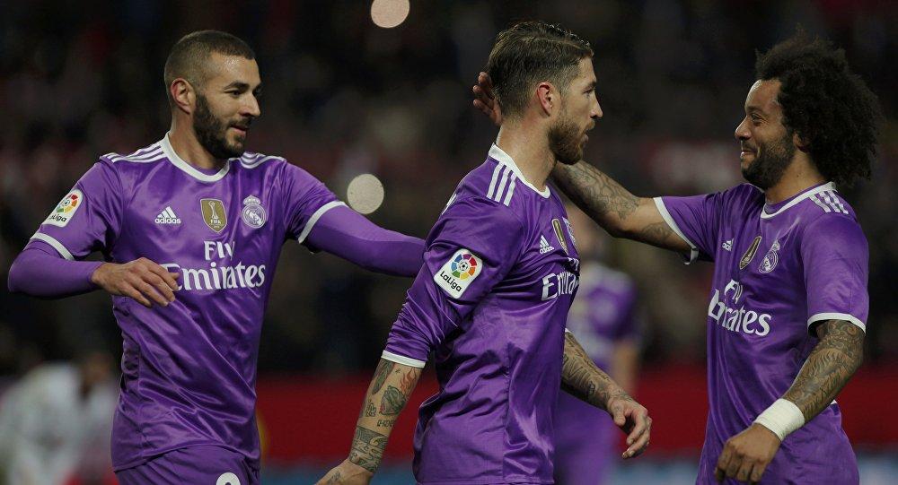 Футболисты ФК Реал Мадрид Серхио Рамос отмечает гол с товарищами по команде Каримом Бензема и Марсело во время матча с Севильей в 1/8 финала Кубка Испании в Севилье