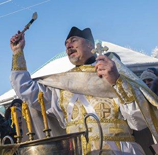 Священник обливает священной водой на церковном празднике крещения Христа.