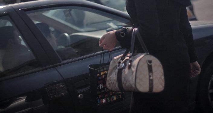 Девушка с сумочной рядом с автомобилем. Архивное фото