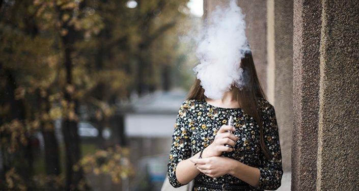 Девушка-вейпер парит электронной сигаретой. Архивное фото