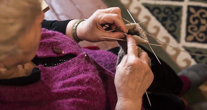 Пожилая женщина шьет в Бишкекском доме-интернате для престарелых