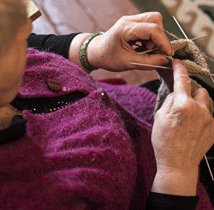 Пожилая женщина шьет. Архивное фото