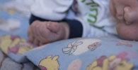 Новорожденный ребенок лежит на кровати. Архивное фото