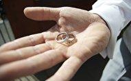 Обручальное кольцо на ладони у мужчины. Архивное фото