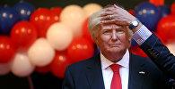 Архивное фото работника музея фиксирует волосы восковой фигуры президента США Дональда Трампа